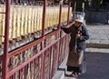 Tibetan woman at the temple prayer wheels