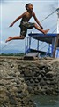 Exuberant Pilippino boy jumps into the sea, Pandan
