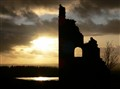 Clouded sun behind ruin Galloway Scotland.