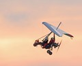 Ultralight  aircraft taking offf at sunset