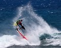 A windsurfer makes a jump and a flip in rough conditions in Hookipa beach, Maui, Hawaii