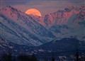 As the sun was setting the full moon was rising over the Chugach Mountains Alaska.