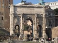 Strong huge old Roman gate contrasting the weakness of tiny people