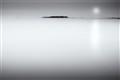 Misty moonrise over open sea