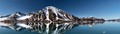 panorama of svalbard snow-covered mountains along calm, reflective arctic ocean
