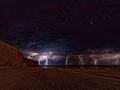 A lightning storm, under a starlit sky