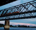 A BNSF Railway freight pulls out of Memphis toward Arkansas near sunset, crossing the oldest bridge spanning the Mississippi River south of St. Louis. That span, known as the Frisco Bridge, opened in 1892 and still carries trains daily on its single set of tracks.