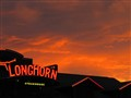 Steakhouse Sign Against Red Sky