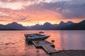 a boat dock on lake mcdonald, glacier np, at sunset