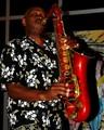 Man playing red saxophone with the Gladezmen….