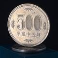 A Japanese ¥500 coin resting atop a ¥50 coin.