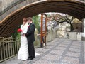 Newlyweds under a bridge in old Prague
