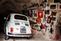 500 Fiat into a natural cave garage.