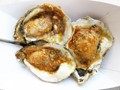 Photo of three oysters in garlic butter sauce bought from an outdoor concession stand.  Photo taken outdoors in the shade with oysters in the paper carry out container.
