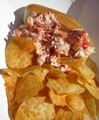 Photo of lobster roll sandwich and potato chips.  Sandwich is stuffed with lobster.