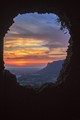 Sunset through a crumbled hole in the wall at the Temple of Jupiter in Terracina Italy.