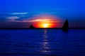Silhouette of sailing boat against sunset