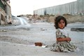 Bethlehem girl sitting near the wall that is separating the West Bank