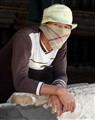 Bagasse worker covers his mouth from the dust