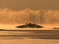 In January the Gulf of Finland is open, so cold weather causes sea smoke. Low sun made the scene look golden