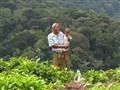 Tea picker takes a break to show her daughter the strange tourists walking by